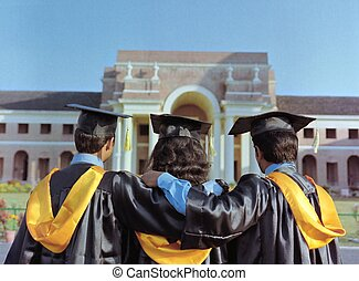 Group of college graduates looking at their campus after graduation ceremony.