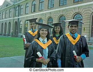 Group of Indian graduate students holding their diploma after graduation