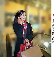 Pretty Indian Woman talking on phone after shopping in a...
