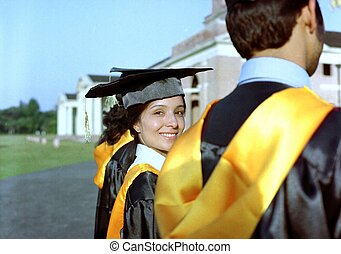 Woman standing out from a graduation group and smiling,