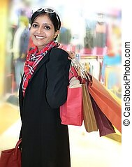 Beautiful Indian shopping woman, happy holding colorful...