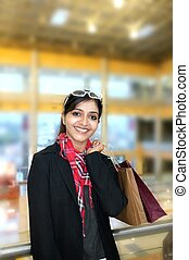 Pretty Indian woman smiling with lots of shopping bags