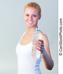 Beautiful woman with a bottle of water with focus on water