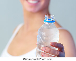 Close-up of a woman with a bottle of water with focus on...