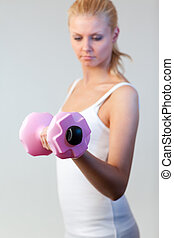 Portrait of a woman trained with weights focus on weights