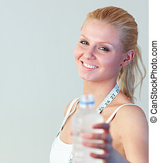 Close-up of a happy woman holding a bottle of water focus on woman