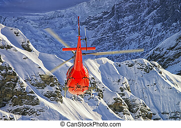 Red helicopter at swiss alps near Jungfrau mountain in...