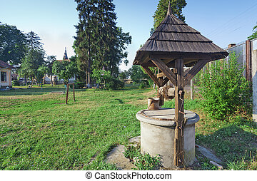 Old water well with bucket and roof
