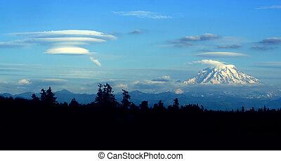 Lenticular cloud forming downwind of Mt. Rainier -...