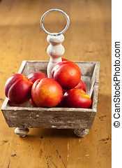 Nectarines - Ripe nectarines waiting to be eaten in a wooden...
