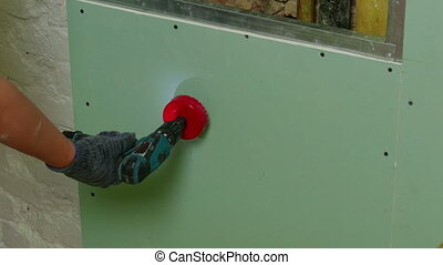 Repairer Make Drilling a Round Hole in a Drywall, closeup