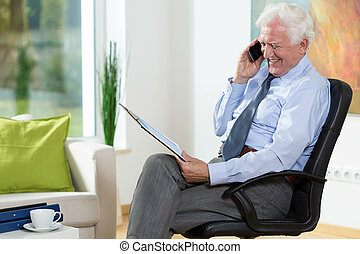 Talking on the phone - Elderly happy man in his office...