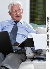 Businessman in home - Elderly elegant businessman working in...