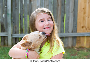 Blond kid girl with chihuahua pet dog playing - Blond kid...