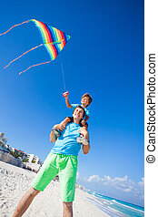 Boy sits on shoulders of dad holding flying kite