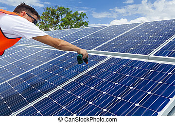 Solar panel installation - Young technician installing solar...