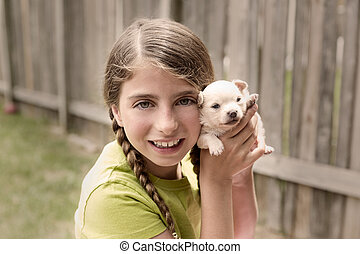 Girl playing with puppy chihuahua pet dog