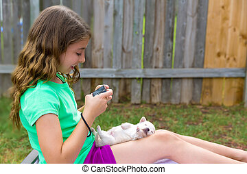 Kid girl taking photos to puppy dog with camera