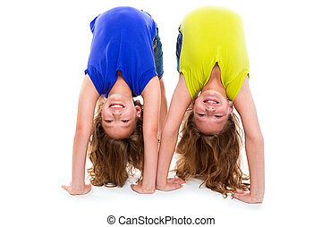twin kid sisters playing as flexible contortionist happy on...