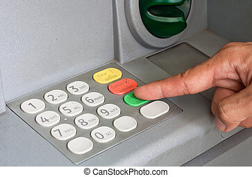 Close-up of hand entering PINpass code on ATMbank machine...
