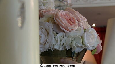 Florist inspects bouquet of pastel roses, close-up