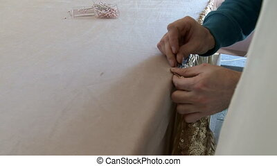 Decorator adorns table with shiny fabric - View of decorator...