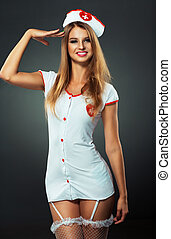 Young and beautiful dancer in nurse costume posing on studio...