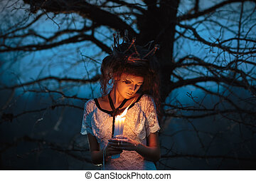 Young girl in the image of a bride with lighted candles in...