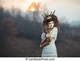 Young girl in a white lace dress, a crown of twigs with a...