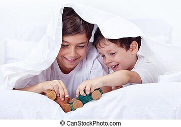 Boys playing in bed with wooden toys - brothers enjoying...