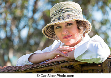 Woman sitting on a bench in the garden - Woman in hat...
