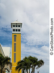 Old Yellow Tower by Palm Trees in Nassau