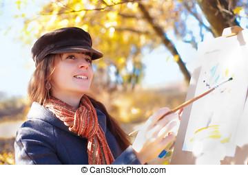 Woman having fun laughing near easel - Young woman having...