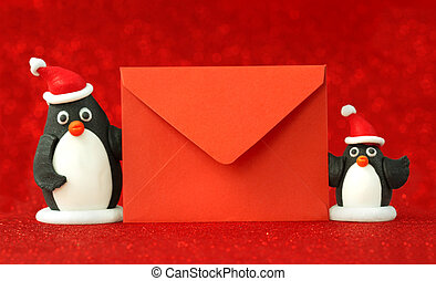 Christmas letter - small penguins holding a red paper...