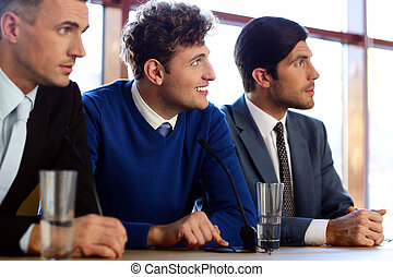 Businessmen communicate at the conference, sitting at the table with microphones