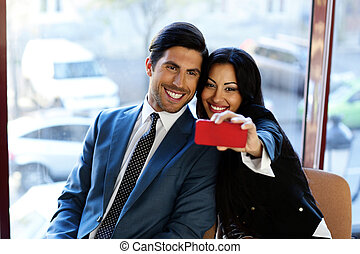 Happy business people making selfie in office