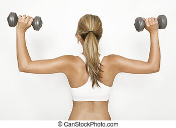 Woman exercising with dumbbells - a woman in a white sports...