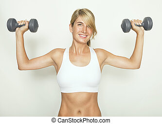 Woman with dumbbells - a woman in a white sports top trained...