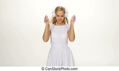 Beautiful female in headphones listening to the music with fluttering on the wind hair over white background