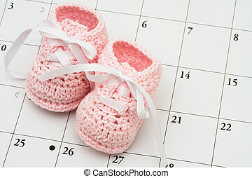 Baby Due Date - Pink baby booties on a calendar background,...