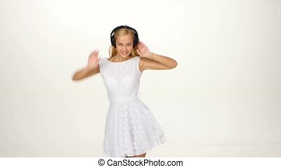 Sexy woman in white shirt listening and dances for the music using headphones