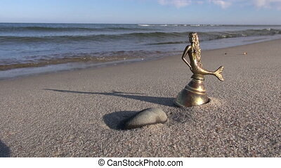 bell with mermaid figure on beach