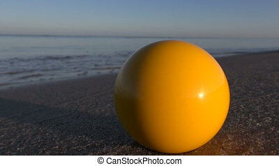 yellow billiards ball on sea beach