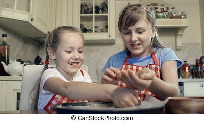 Little Confectioners - Two little girls pouring ingredients...