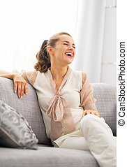 Smiling young housewife sitting in living room