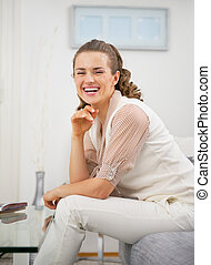 Smiling young woman sitting in living room