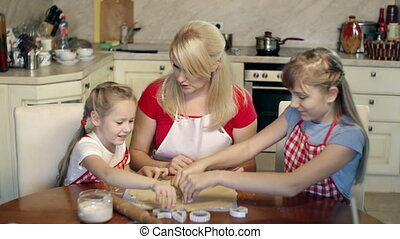 Little Chefs - Mother and daughters shaping cookies with...