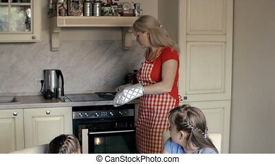 Right Off the Stove - Tilt down of mother treating daughters...