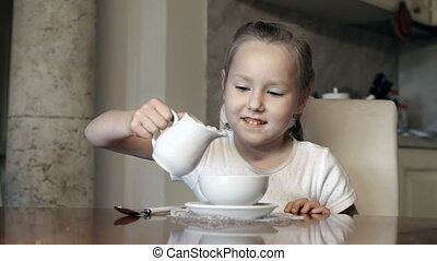 White Tea - Little girl pouring light cream in her cup of...