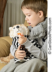 little boy feeds medicinal syrup the toy dog and says AAA...